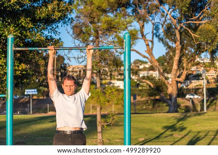 Fit muscular man doing pull ups in outdoor park