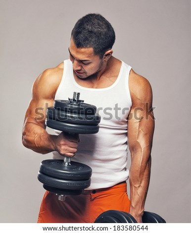 Fit muscular man exercising with dumbbells - stock photo