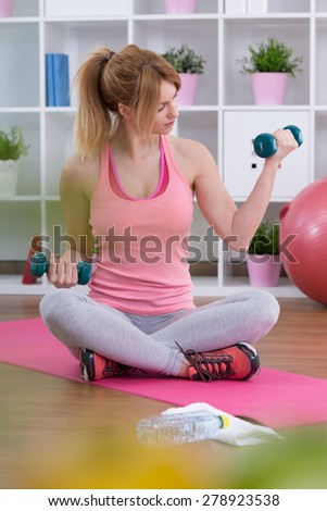 Fit muscular woman working on biceps with dumbbell