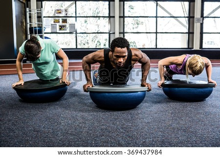 Fit people doing bosu push ups in crossfit - stock photo
