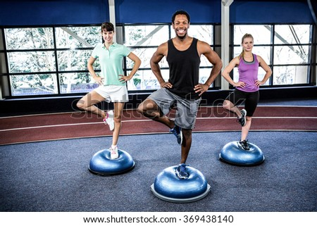 Fit people doing exercise with bosu ball in crossfit - stock photo
