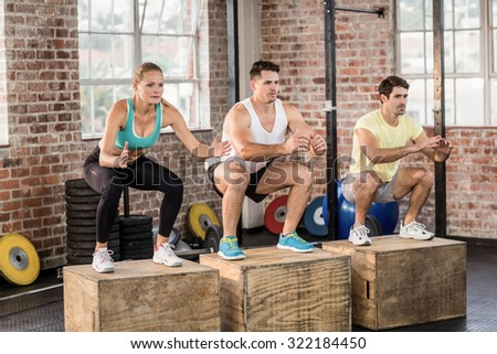 Fit people doing jump box in crossfit gym - stock photo