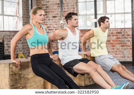 Fit people doing some exercises with box in crossfit gym - stock photo