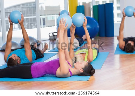 Fit people exercising with medicine ball in fitness studio - stock photo