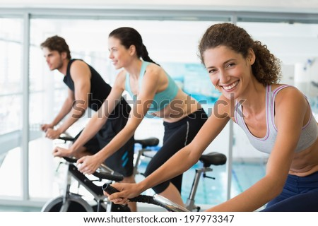 Fit people in a spin class with woman smiling at camera at the gym