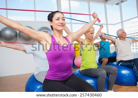 Fit people on fitness balls exercising with resistance bands in gym - stock photo