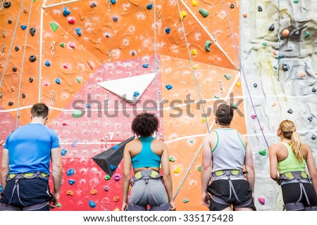 Fit people ready to rock climb at the gym - stock photo