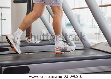 Fit people running on treadmills at the gym