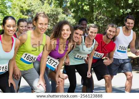 Fit people running race in park on a sunny day - stock photo