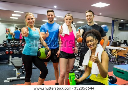 Fit people smiling at camera in weights room at the gym - stock photo