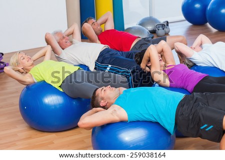 Fit people stretching on exercise balls in fitness club - stock photo