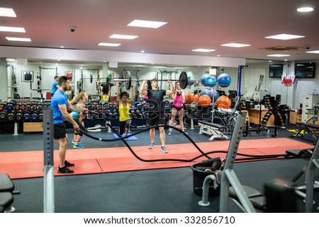 Fit people working out in weights room at the gym - stock photo