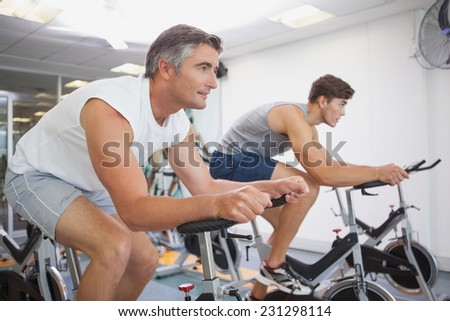 Fit people working out on the exercise bikes at the gym - stock photo