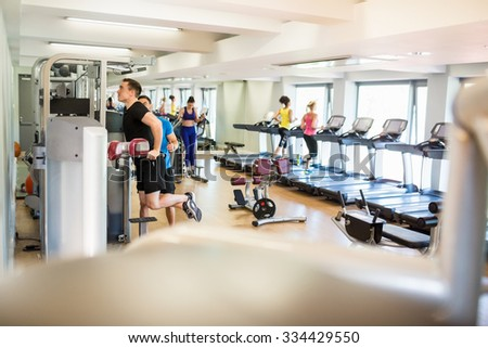 Fit people working out using machines at the gym - stock photo