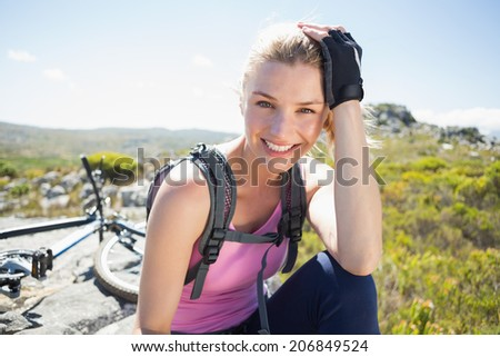 Fit pretty cyclist taking a break on rocky peak smiling at camera on a sunny day - stock photo