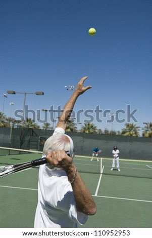 Fit senior man serving tennis ball on court