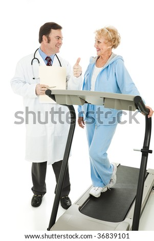 Fit senior woman on treadmill gets a thumbs up from her doctor.  Isolated on white. - stock photo