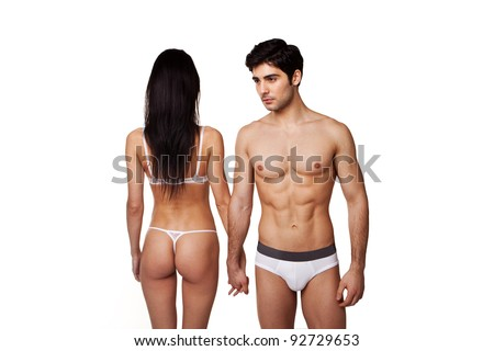 Fit Sexy Couple In Underwear standing side by side with the man facing forwards and the woman facing away, studio on white