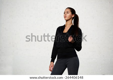 Fit sexy woman dressed in sportswear posing outdoors on white wall background, young healthy woman enjoying the sun ready for workout, gorgeous girl with fit beautiful figure posing outside - stock photo