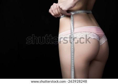 Fit sexy woman in cotton lace underwear with perfect curves.Slimming woman holding  tape/ meter,measuring her waist.Healthy nutrition,fat lose,liposuction,healthy lifestyle and sport concept - stock photo