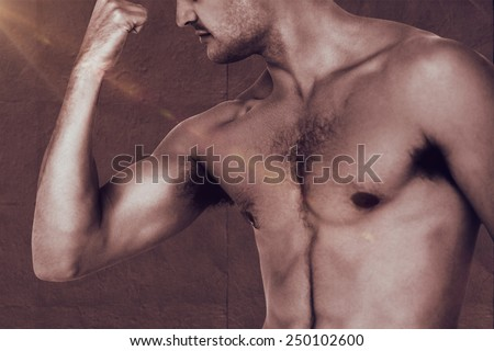 Fit shirtless man flexing his bicep against grey concrete tile