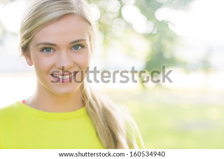 Fit smiling blonde looking at camera in a park on a sunny day