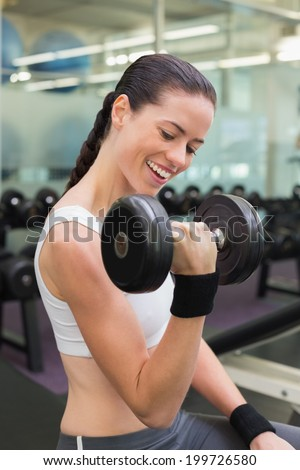 Fit smiling brunette lifting heavy black dumbbell at the gym