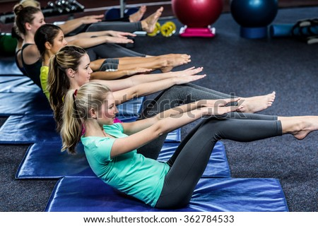 Fit smiling group working abs in gym