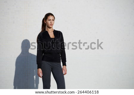 Fit smiling woman dressed in sportswear posing outdoors on white wall background, young healthy woman enjoying the sun ready for workout, gorgeous girl with fit beautiful figure posing outside - stock photo