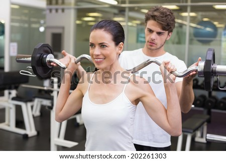 Fit smiling woman lifting barbell with her trainer at the gym