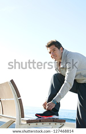 Fit sports man tying his trainers shoe laces, getting ready for exercising, leaning on a wooden bench against a bright blue sky. - stock photo