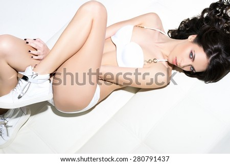 Fit, sporty and sexy young woman in swimsuit and sneakers posing on a sofa