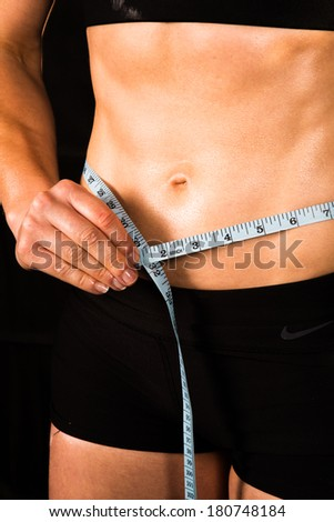 Fit sporty female trainer working out and measuring six pack - stock photo