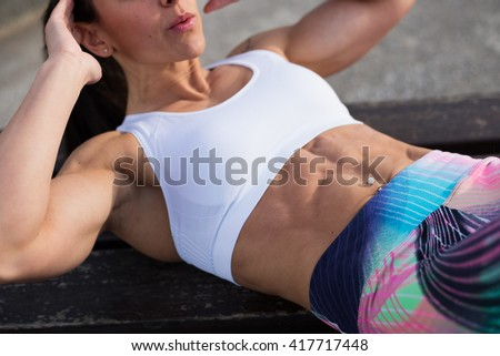Fit strong stomach abdominal muscles closeup. Fitness woman doing crunches exercise workout. Female fit athlete training midsection for  improve core strength. - stock photo
