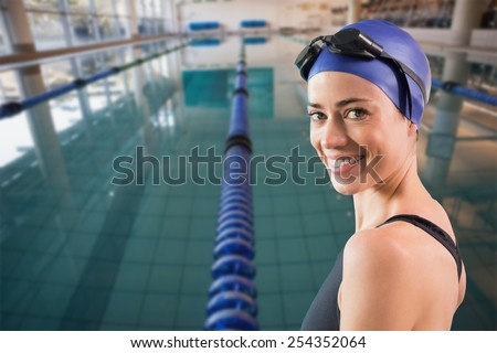 Fit swimmer standing by the pool smiling at camera against empty swimming pool with lane markers - stock photo