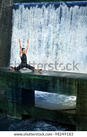 Fit white man doing the splits on concrete footbridge at the waterfall