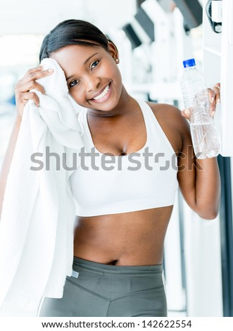 Fit woman at the gym drying her sweat with a towel - stock photo
