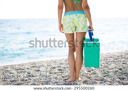 Fit woman carrying cooler box,portable fridge on the beach.Fit slim healthy woman in flower shorts for going to the beach with cooler with healthy food and drinks.Carrying food and drinks to the beach - stock photo