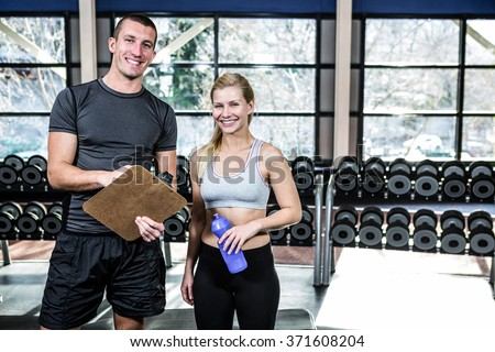 Fit woman discussing performance with trainer at gym - stock photo