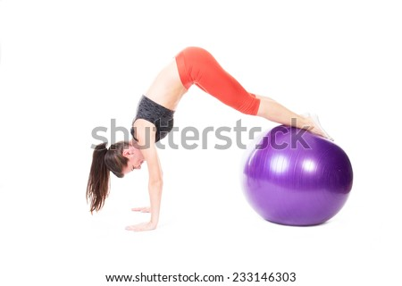 Fit woman doing pike on purple exercise ball - isolated on white.