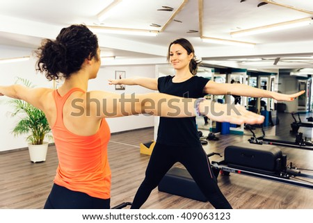 Fit woman doing pilates exercises with her trainer in a gym