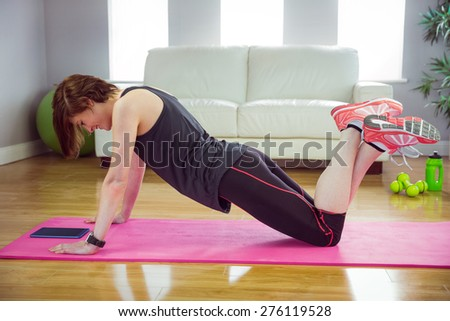 Fit woman doing press up on mat at home in the living-room - stock photo