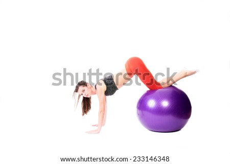 Fit woman doing push-ups on a purple fitness ball - isolated on white.