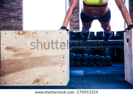 Fit woman doing push ups on fit box at gym - stock photo