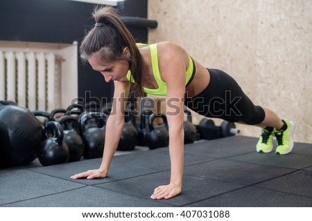 fit woman doing push-ups on the floor, sporty female working out abs, arm muscles - stock photo