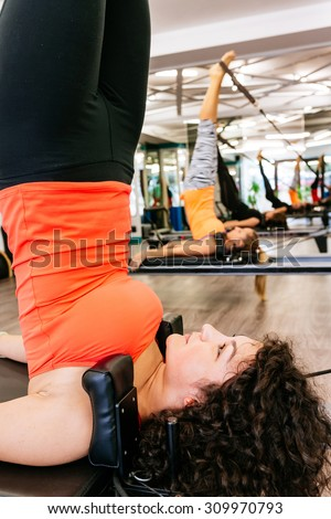 Fit woman doing shoulder stand in a pilates room