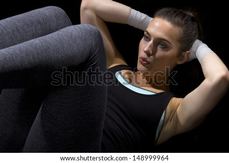 fit woman doing situps on a black background - stock photo