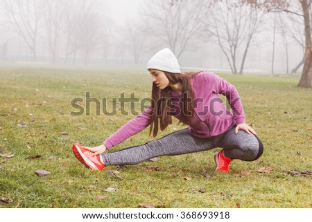 Fit Woman, doing stretching exercise,  healthy lifestyle concept, outdoor activity , winter season
