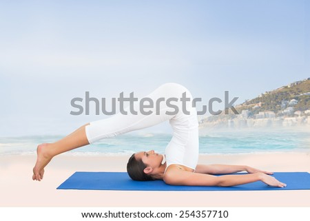 Fit woman doing the plough posture in fitness studio against beautiful beach and blue sky - stock photo