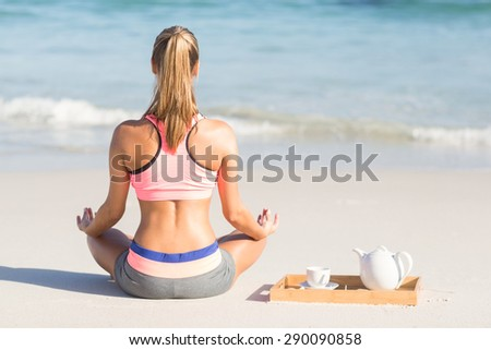 Fit woman doing yoga beside the sea at the beach - stock photo